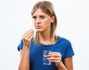 photo-of-a-woman-holding-a-glass-of-water-and-pill.jpg