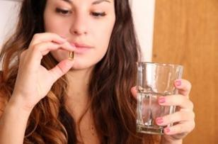 woman-holding-a-glass-of-water-and-supplement.jpg