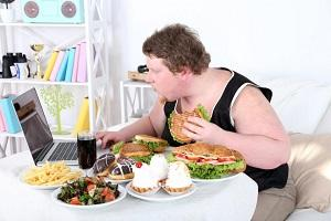 photo-of-obese-man-eating-junk-foods-while-using-laptop.jpg