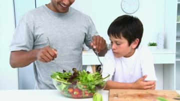 man-preparing-salad-with-son.jpg