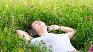 woman-listening-music-lying-on-the-field.jpg