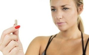 Woman Holding and Staring at Pill