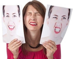Woman Holding Two Pictures of Her Face